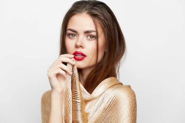 スカーフを持つ女性が顔の近くで手を握るチャーム赤い唇のクロップドビュー