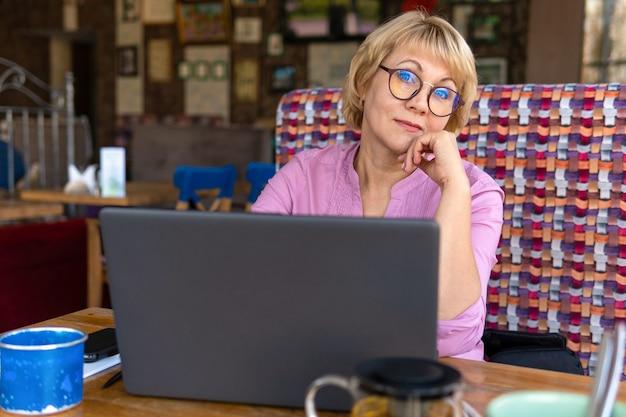노트북을 가진 여성이 사무실에서 일하고 있습니다. 중년 사업가가 카페에 있다. 그녀는 웃으면서 놀란 표정을 짓는다