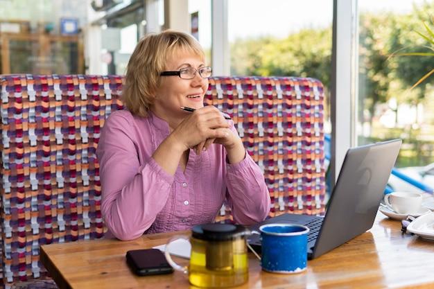 노트북을 가진 여성이 사무실에서 일하고 있습니다. 중년 사업가가 카페에 있다. 그녀는 미소를 지었다.
