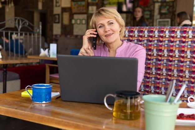 노트북을 가진 여성이 사무실에서 일하고 있습니다. 중년 여성은 카페에서 일하는 사업가입니다. 그녀는 미소를 지었다. 그녀는 전화 중입니다.그녀는 컴퓨터를 봅니다.