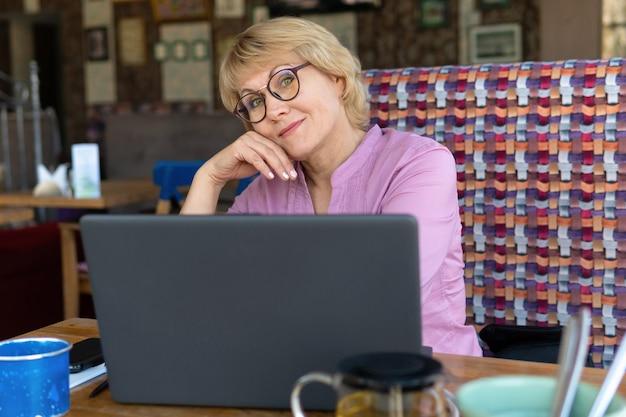 노트북을 가진 여성이 사무실에서 일하고 있습니다. 중년 여성은 카페에서 일하는 사업가입니다. 그녀는 미소를 지었다.