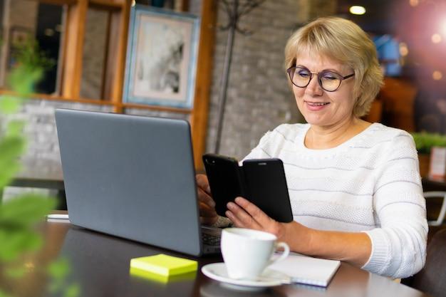 노트북을 가진 여자는 사무실에서 일하고있다
