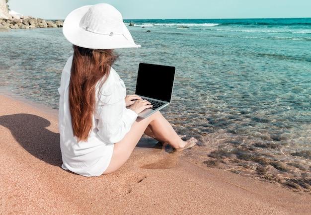 Женщина с ноутбуком на песке отдыхает и работает фрилансером