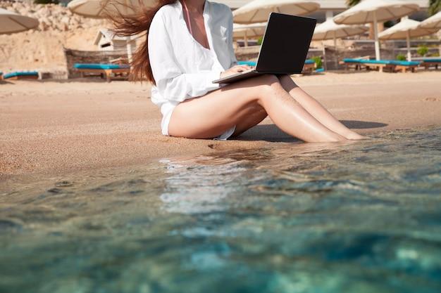 砂の上にラップトップを持っている女性が休んでいて、フリーランサーとして働いています