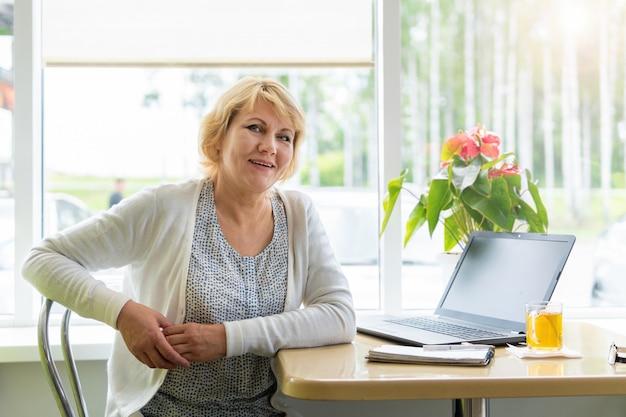 노트북을 가진 여성이 사무실의 카페에서 일하고 프리랜서이자 사업가입니다