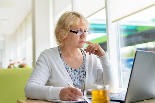 노트북을 가진 여성이 사무실의 카페에서 일하고 프리랜서입니다.