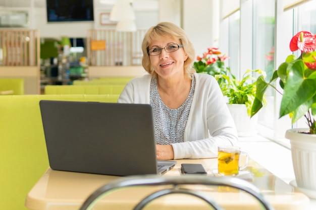 노트북을 들고 사무실 카페에서 일하는 여성
