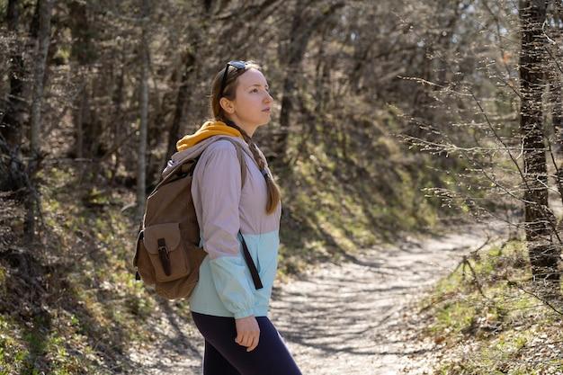 森のハイキングや旅行で大きなハイキングバックパックを持っている女性