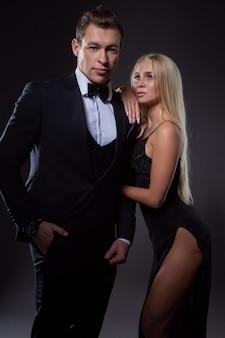 검은 이브닝 드레스에 가벼운 머리를 가진 여자와 나비 넥타이와 양복을 입은 잘 생긴 남자