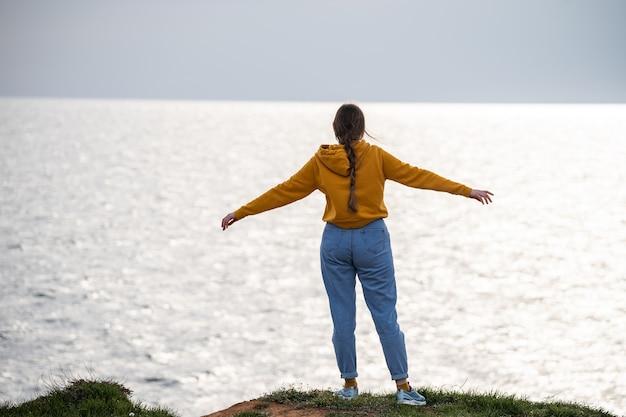 Женщина с длинной косой раскинула руки в стороны и любуется морским пейзажем чудесным видом на море ...