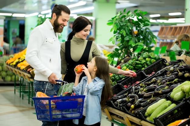 Женщина с мужчиной и ребенком выбирают овощи во время покупок в овощном супермаркете