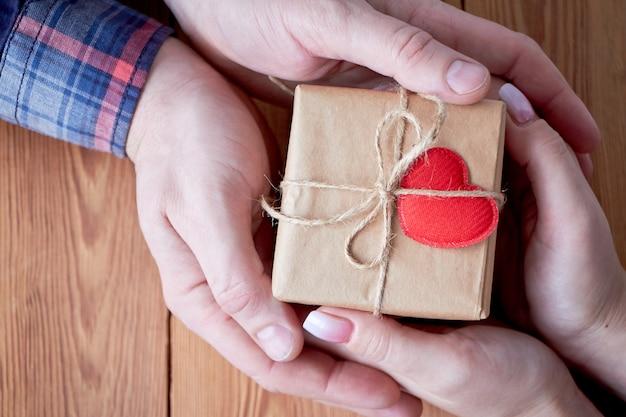 Женщина с мужчиной держит в руке подарок