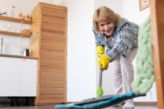 モップを持った女性が台所を掃除する