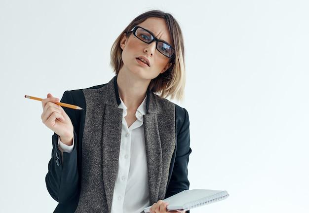 Женщина с блокнотом и ручкой в руках на светлом фоне делового финансового костюма