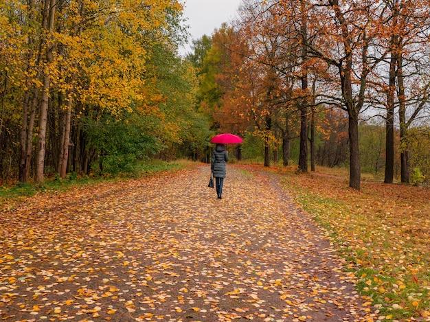 赤い傘をさした女性が一人で秋の公園を歩いています。