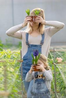 小さな娘を持つ女性は、春に温室で鉢植えの花を飼っています。