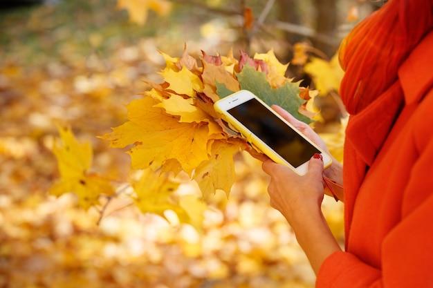스마트폰과 밝은 단풍잎을 가진 여성이 화창한 가을날 공원에서 걷고 있다