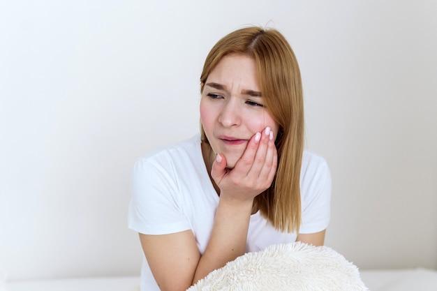 歯痛のある女性がベッドに座り、医者を待っています。若い白人女性は、敏感な歯、歯痛、虫歯、または歯周病を患っています。健康と病人の概念。