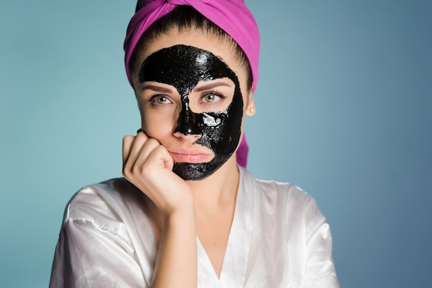 シャワーを浴びた後、頭にタオルをかぶった女性がフェイスマスクを着用