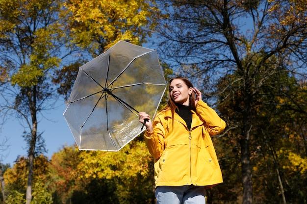 晴れた日の秋の気分で秋の黄色の木々の前で透明な傘を持つ女性が微笑む