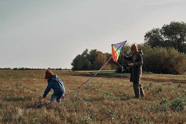 2歳の子供を持つ女性が凧を飛ばしています。子供とのゲーム、母性。