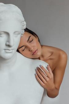 Женщина с ухоженным лицом и телом стоит возле бюста скульптуры женщины.