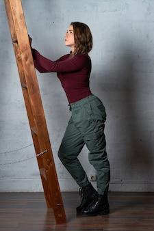 나무 사다리를 가진 여자는 흰색 벽돌 벽에 서
