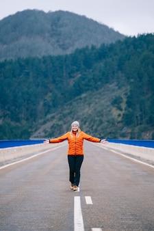 ウールの帽子とオレンジ色のコートを着た女性が走り、山を背景にした道を飛び降りる