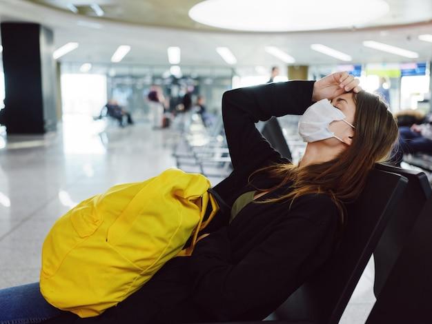 黄色いバックパックを背負った女性が空港に座って飛行機を待っている