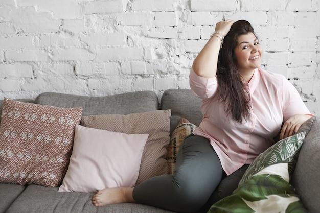 Женщина с красивым телом позирует на диване