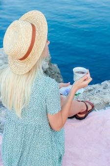 Женщина со светлыми волосами в шляпе сидит на берегу моря со стаканом в руках.