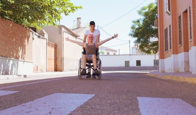 がんの女性が車椅子に座っています。彼女は彼氏と一緒に通りを歩いている。彼らは面白いし、彼らは笑います。彼らは中庭を歩く