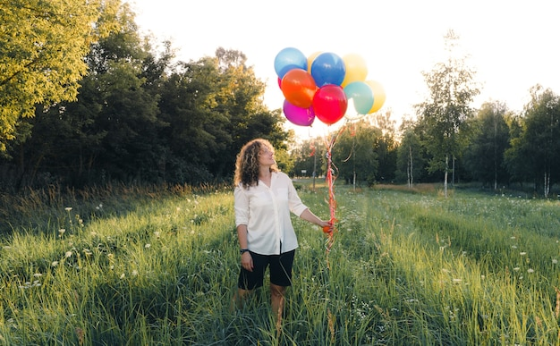 곱슬 머리를 가진 여자는 그녀의 손에 무지개 풍선을 보유하고 있습니다. 공원에서 잔디에 젊은 아름 다운 소녀.