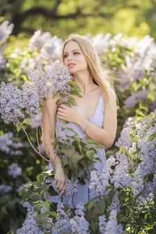 花に囲まれた草原でかわいい顔の形と軽い化粧をした女性
