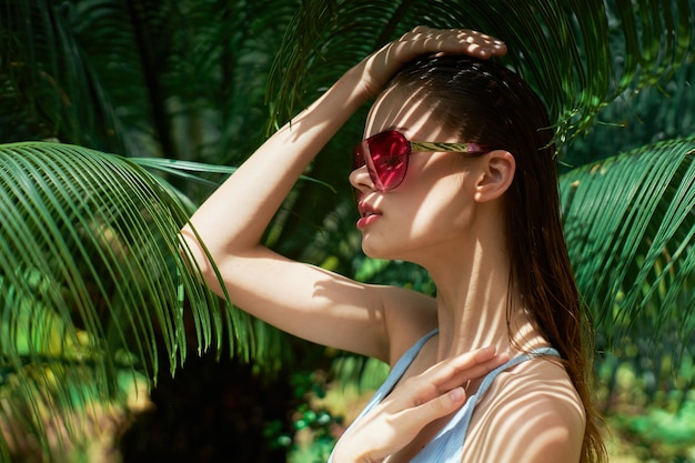 ヤシの木の緑の葉の近くに眼鏡をかけている女性が頭に手をかざしています。高品質の写真