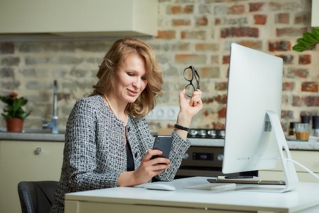 眼鏡をかけた女性がスタジオのデスクトップコンピューターでリモートで作業しています。自宅でのビデオ会議中にスマートフォンに気を取られた上司。幸せな教授は、オンライン講義の前に携帯電話を使用しています。
