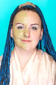 파란색 표면에 녹색 점토 마스크에 그녀의 얼굴의 절반을 가진 여자