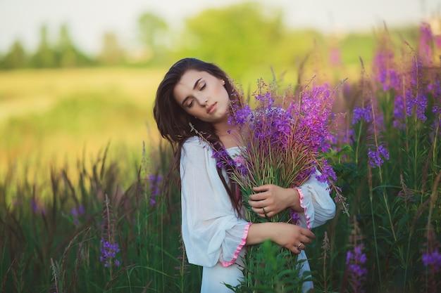 目を閉じてラベンダー畑でポーズをとる女性