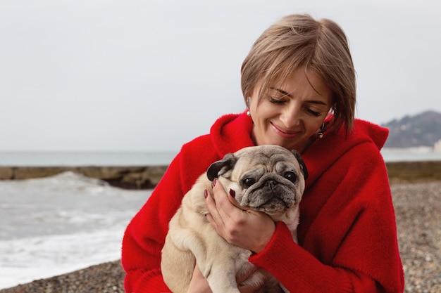 お気に入りのパグを腕に抱えた女性。冬の海沿いの肖像画。