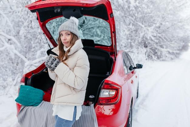 雪の降る冬の森の中で、ホットコーヒーを片手に赤い車に座っている女性。ホットコーヒーのカップを持つ女の子は、開いたトランクの車に座っています