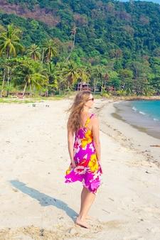 긴 금발 머리를 한 여성이 태국의 열대 섬 코창(koh chang)의 모래 해변을 따라 걷고 있습니다. 여행과 관광.