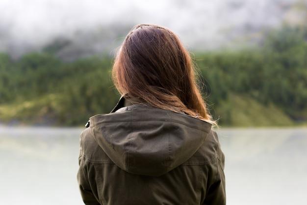 長い髪の女性が背中を背負って立って山の雨天を眺める