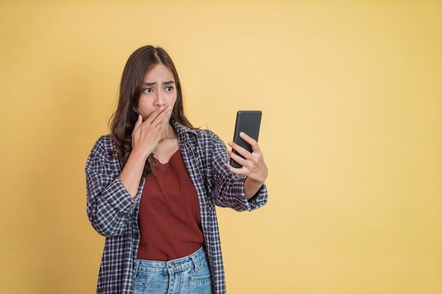 휴대전화를 사용하는 긴 머리를 가진 여성이 카피스페이스가 있는 휴대전화 화면을 보고 놀란다