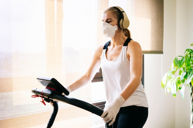 マスクと手袋のスリムなアスリートの女性がトレッドミルで実行されている自宅で運動をします
