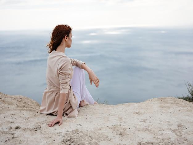石の丘と海を背景に、上着を着た女性が座っています。高品質の写真