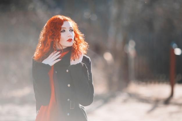 秋の背景に黒いコートを着た赤い巻き毛の女性。薄い肌と青い目、首にスカーフが付いた明るく珍しい外見の赤い髪の少女。ストリートスタイル