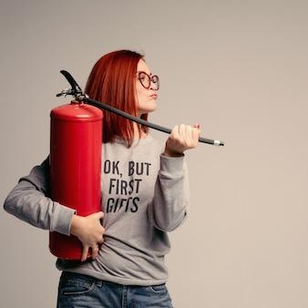 Женщина с рыжими волосами держит огнетушитель. эмоциональная яркая женщина гасит все с помощью огнетушителя.