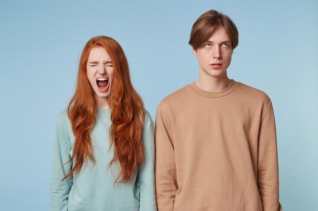 赤い長い髪の女性が目を閉じて立って、叫んでいるかのように口を大きく開いて、隣の男が耳を傾けるのに飽き飽きしている。