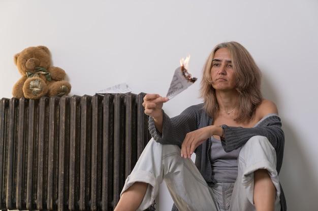 うつ病の兆候のある女性がバッテリーの隣のアパートの床に座って、紙で作られた火に設定された飛行機を持っています