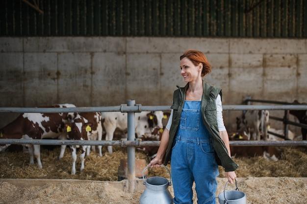 Работница с консервными банками работает на молочной ферме, сельском хозяйстве.